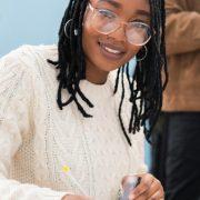 Taxonomia de Bloom: fotografai de um grupo de estudantes sentados em uma mesa e conversando.