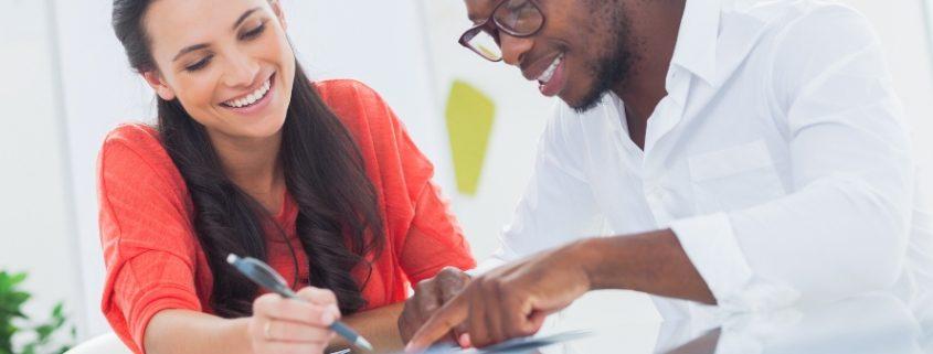 Comissão Própria de Avaliação: fotografia de um homem e uma mulher sorrindo e fazendo anotações.