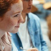 Educação dialógica: fotografia de um grupo de estudantes conversando. O foco está em uma estudante sorrindo.
