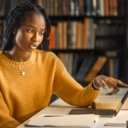 Educação digital: fotografia de duas mulheres em uma biblioteca estudando e analisando algo na tela de um notebook.
