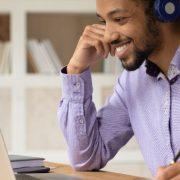 Educação do futuro: fotografia de um homem anotando algo enquanto olha para a tela do notebook e sorri.