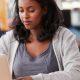 Experiência do aluno através do ensino com as mídias: fotorafia de uma estudante sentada à mesa e utilizando o computador.