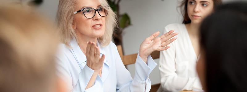 Projeto Pedagógico de Curso: fotografia de um grupo de pessoas em uma reunião ao redor de uma mesa. Uma mulher está falando.
