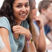 Atividades para alunos com dislexia: fotografia e estudantes em uma sala de aula, foco em uma estudante sorrindo para a câmera.