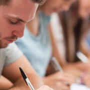 Atividades para alunos com TDAH: fotografia de uma sala de aula com foco em uma fileira de alunos escrevendo.