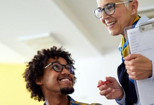 Competências e habilidades pedagógicas: fotografia de uma professora auxiliando dois alunos. Todos sorriem.