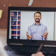 Tutor EaD: fotografia de uma pessoa assistindo a uma aula online com foco na tela do notebook.