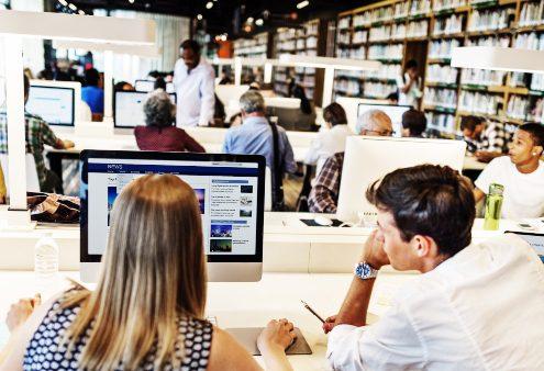 Infraestrutura educacional: fotografia de uma biblioteca bem equipada com diversos alunos.