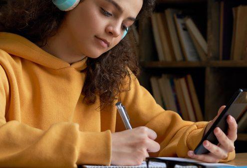 Mobile Learning: fotografia de uma mulher utilizando o celular para estudar.